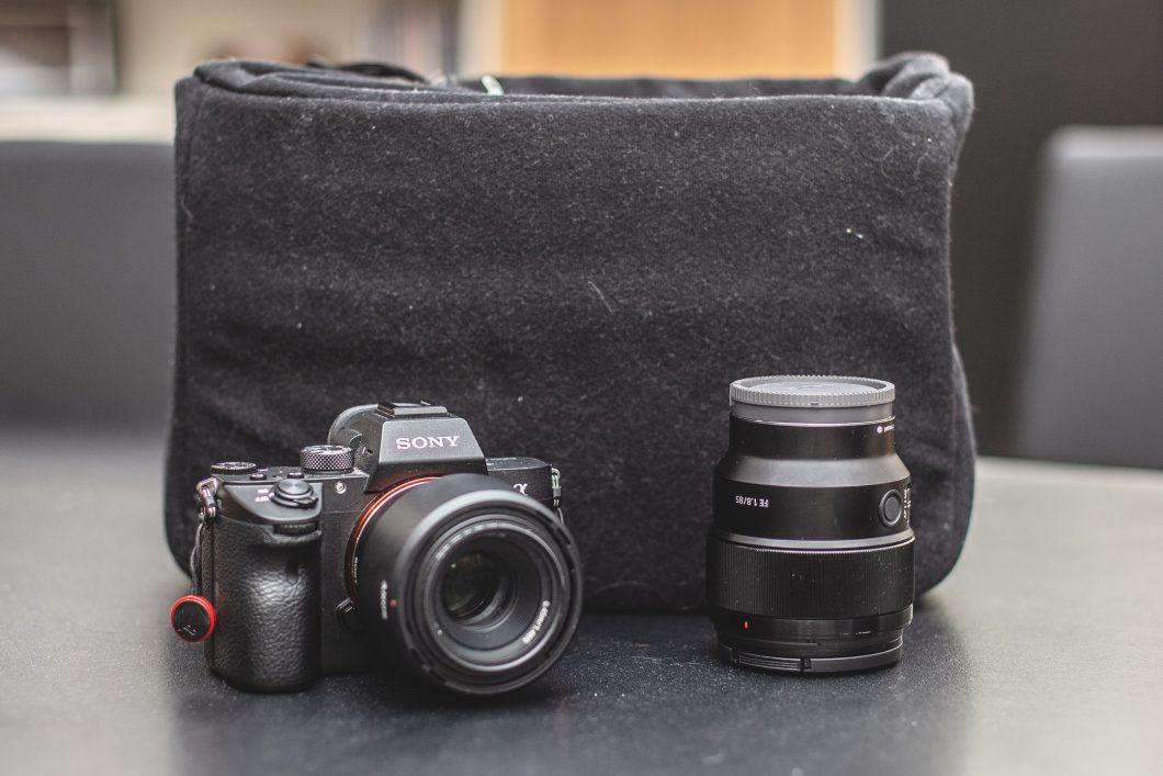 En Sony a7III tillsammans med ett objektiv från Sony som är 85mm med 1.8 bländare. Bakom dem står en väskinläggning från Matin.